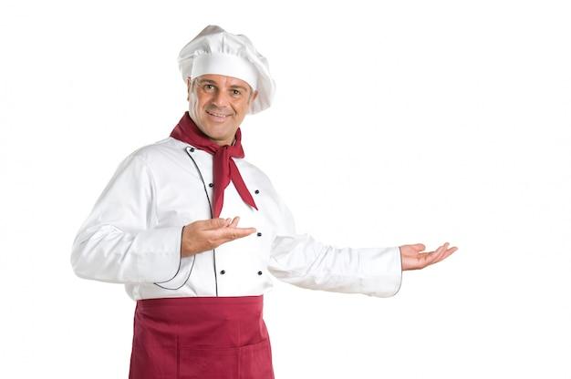 Glücklicher lächelnder koch, der ihre rezepte und produkte lokalisiert auf weißem hintergrund präsentiert