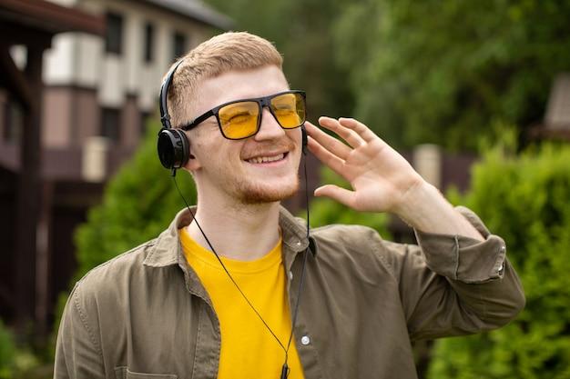 Glücklicher lächelnder mann in den kopfhörern hören positive musik mit geschlossenen augen, natur. sommerferien-wiedergabeliste, klänge der freiheit reiseinspirationsträume, gewinnerkonzept. kopieren sie den textbereich
