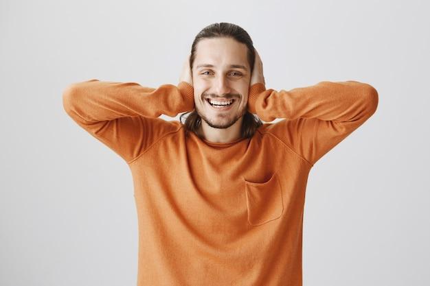 Glücklicher lächelnder mann schloss ohren mit händen