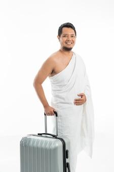 Glücklicher lächelnder muslimischer mann mit koffer, der für hadsch geht