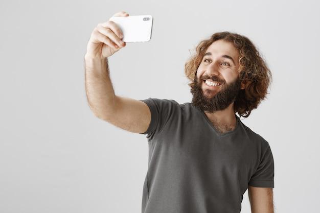 Glücklicher lächelnder nahöstlicher mann, der selfie mit smartphone nimmt