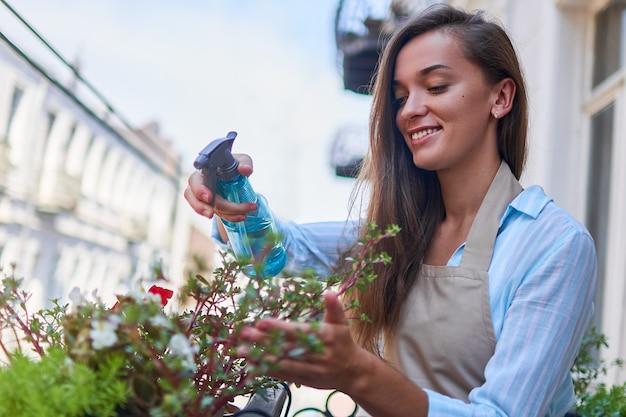 Glücklicher lächelnder niedlicher fraugärtner, der schürze tränkt balkonblumen unter verwendung der sprühflasche