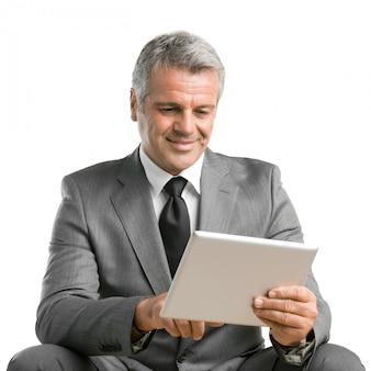 Glücklicher lächelnder reifer geschäftsmann, der das netz surft und mit digitalem tablett lokalisiert auf weißem hintergrund arbeitet