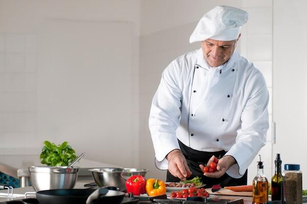 Glücklicher lächelnder reifer koch, der eine mahlzeit mit verschiedenen gemüsen vorbereitet