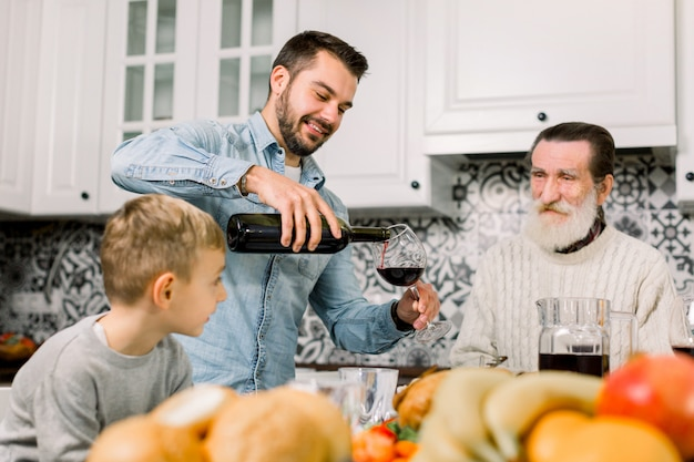 Glücklicher lächelnder vater, der wein in gläser für seine familie am feiertagsessen gießt. randvater, vater und kleiner sohn sitzen im hellen esszimmer am tisch