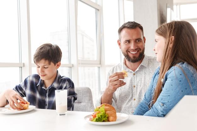 Glücklicher lächelnder vater mit kindern 8-10, frühstück zusammen in der hellen küche zu hause und croissant-sandwiches essend