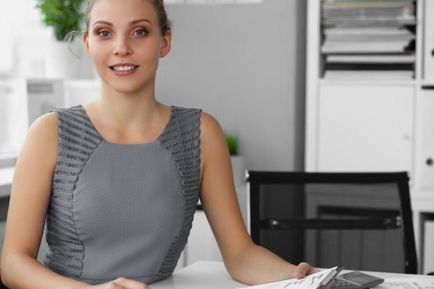 Glücklicher lächelnder weiblicher angestellter, der mit dokumenten arbeitet