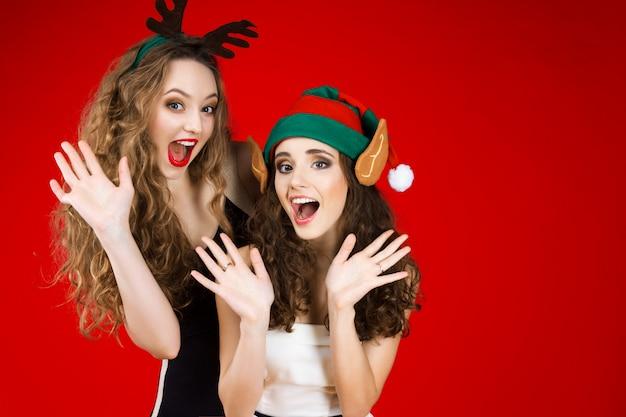 Glücklicher lächelnder weiblicher erwachsener der jungen schönheiten, der das märchengrün-weihnachtselfenhutohr-rotwildhörner-kleine schwarze weiße kleid feiert winterurlaubpartei des neuen jahres trägt