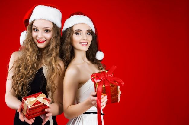 Glücklicher lächelnder weiblicher erwachsener der jungen schönheiten, der märchen santa christmas-hut wenig schwarzes weißes kleid feiert die lokalisierten winterurlaub-partei-griffgeschenke des neuen jahres trägt
