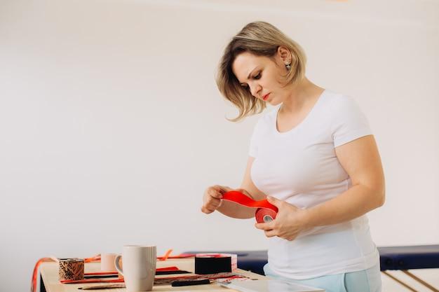 Glücklicher lächelnder weiblicher therapeut, der kinesiologieband rollt und sich auf medizinische beratung in der klinik vorbereitet.