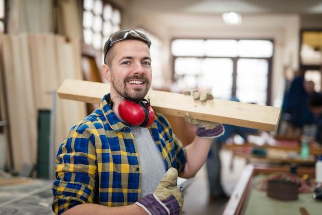 Glücklicher lächelnder zimmermann, der holzmaterial und daumen in seiner tischlerei hält