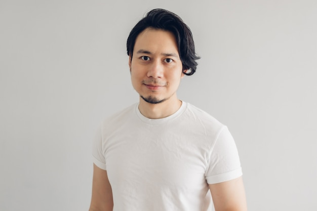 Glücklicher lächelngesichtsmann mit langen schwarzen haaren und weißem t-shirt