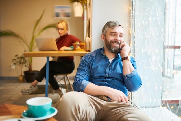 Glücklicher lässiger grauhaariger mann, der durch fenster im gemütlichen café entspannt und mit jemandem per smartphone spricht
