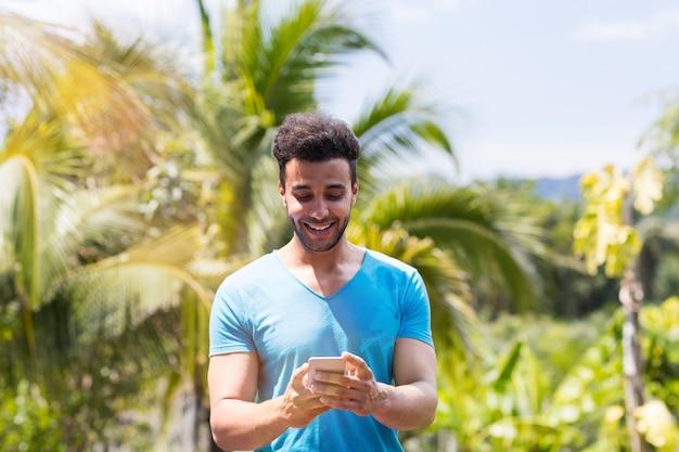 Glücklicher lateinischer mann, der zellintelligentes telefon online über tropischem forest background, porträt des jungen kerls verwendet