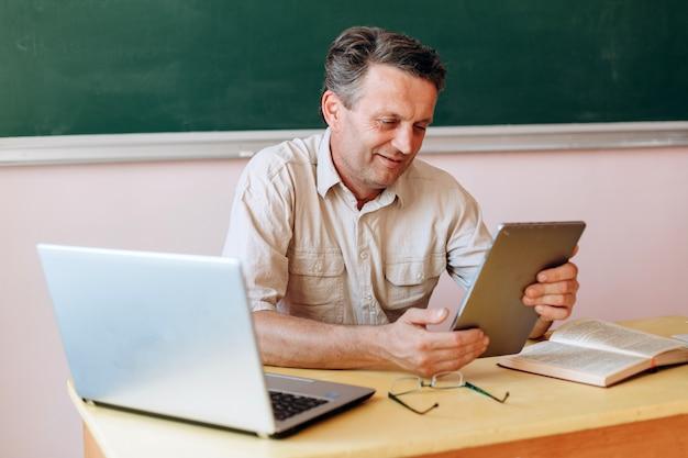 Glücklicher lehrer, der eine tablette hält und den schirm betrachtet