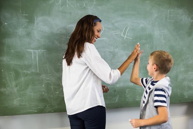 Glücklicher lehrer und schuljunge, die hoch fünf im klassenzimmer gibt