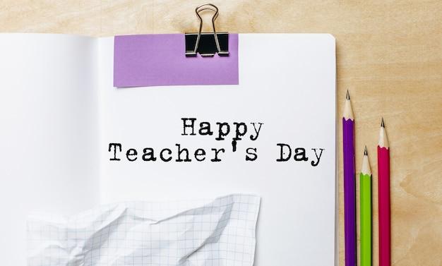 Glücklicher lehrertagstext geschrieben auf einem papier mit stiften auf dem schreibtisch im büro