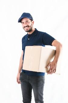 Glücklicher lieferbote mit paket auf weißem hintergrund