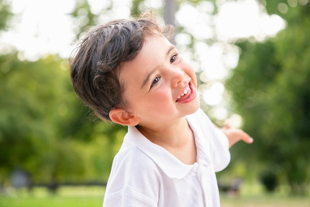 Glücklicher lustiger entzückender junge tanzt, lacht, hat spaß im sommerpark, lächelt und schaut weg. nahaufnahme. kindheitskonzept