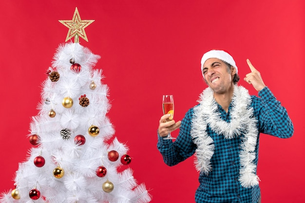 Glücklicher lustiger junger mann des emotionalen comics mit weihnachtsmannhut in einem blauen gestreiften hemd, das ein glas wein hält