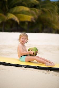 Glücklicher lustiger kleiner vorschulkindjunge, der kokosnusssaft am ozeanstrand trinkt