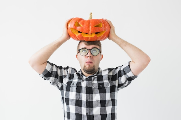 Glücklicher lustiger mann, der eine kürbislaterne hält, schnitzte halloween-kürbis im hellen raum.