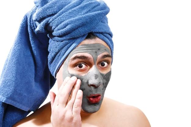 Glücklicher lustiger mann mit maske für haut, blaues handtuch auf dem kopf, ernster mann, mann verwöhnt, isoliertes foto,