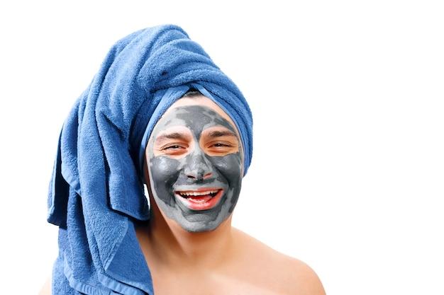 Glücklicher lustiger mann mit maske für haut, blaues handtuch auf dem kopf, mann lächelt, isoliertes foto,