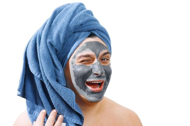 Glücklicher lustiger mann mit maske für haut, mann mag, eine maske für die haut zu machen