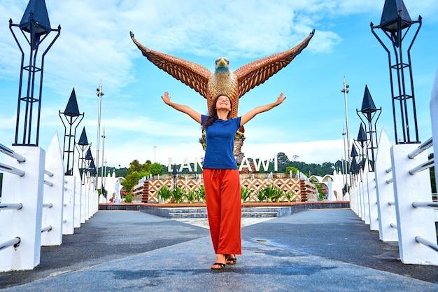 Glücklicher mädchen-tourist, der neben skulptur eines roten adlers aufwirft, der seine flügel ausbreitet. beliebter touristenort auf der insel langkawi.