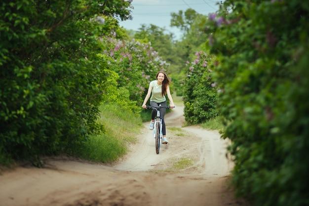 Glücklicher mädchenradfahrer, der draußen auf eine mountainbike fährt. abenteuerreisen.