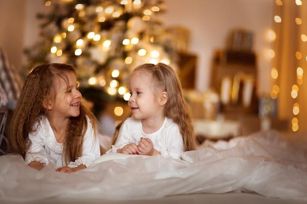 Glücklicher mädchenschwesterhintergrund von goldenen bokeh weihnachtslichtern