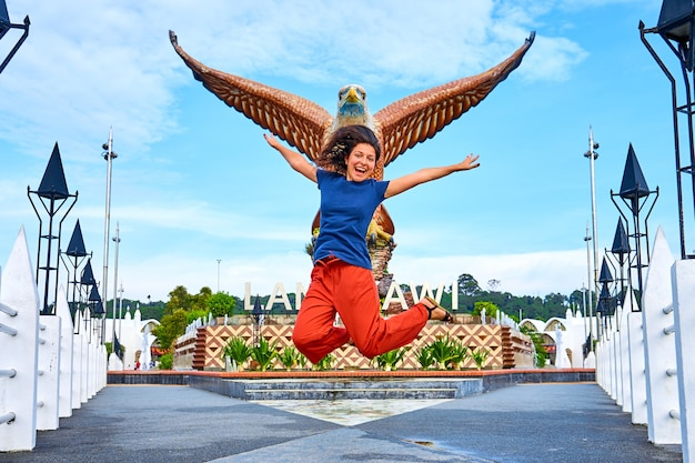 Glücklicher mädchentourist, der nahe bei der skulptur eines roten adlers aufwirft, der seine flügel ausbreitet. beliebter touristenort auf der insel langkawi