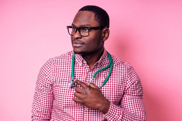Glücklicher männlicher afrikanischer medizinischer chirurg kardiologe arzt in einem weißen mantel auf einem rosa hintergrund im studio.