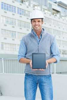 Glücklicher männlicher architekt, der draußen digitale tablette zeigt