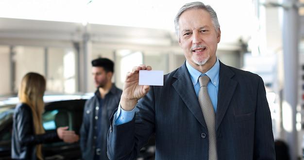 Glücklicher männlicher autohändler, der eine visitenkarte hält