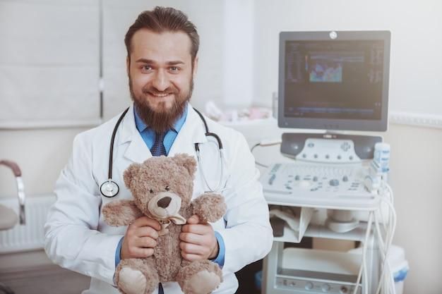 Glücklicher männlicher bärtiger arzt, der zur kamera lächelt und plüsch-teddybärspielzeug hält