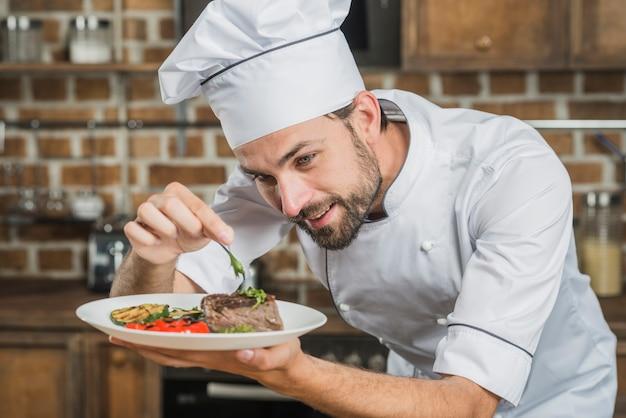 Glücklicher männlicher chef, der rindfleischsteak mit gemüsedekoration zubereitet