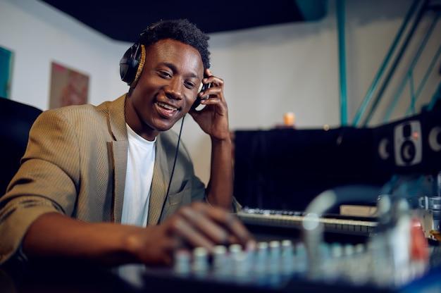 Glücklicher männlicher dj in kopfhörern, aufnahmestudioinnenraum im hintergrund. synthesizer und audiomixer, musikerarbeitsplatz, kreativer prozess