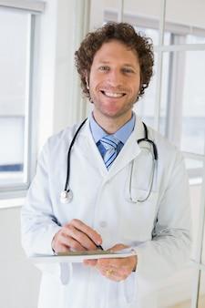 Glücklicher männlicher doktor mit klemmbrett im krankenhaus