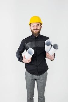 Glücklicher männlicher erbauerarchitekt, der plan gegen weißen hintergrund hält