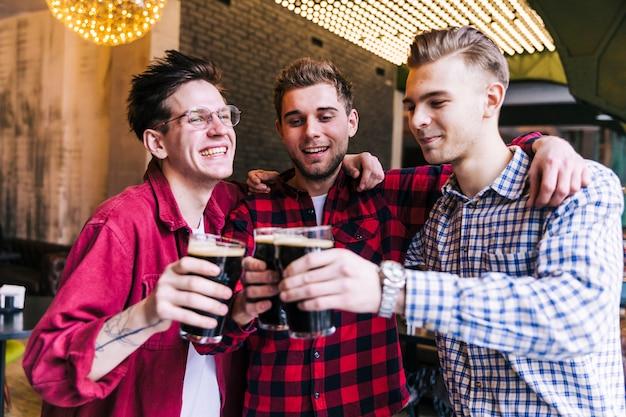Glücklicher männlicher freund, der beifall mit biergläsern macht