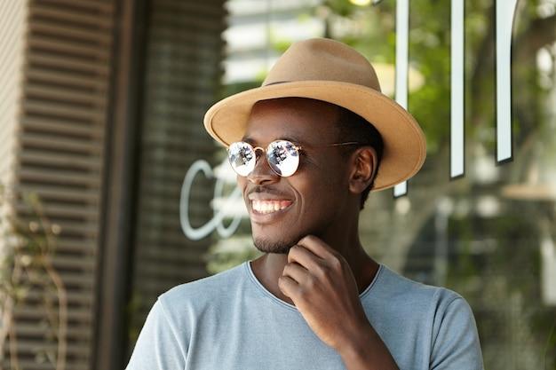 Glücklicher männlicher junge, der am straßencafé am sonnigen sommertag entspannt
