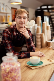 Glücklicher männlicher kellner in schürze mit tasse heißem getränk im café, barista arbeitet gerne in der cafeteria