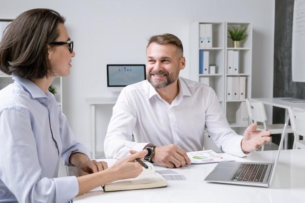 Glücklicher männlicher makler, der auf laptop-anzeige zeigt, während präsentation zu seinem kollegen beim arbeitstreffen macht