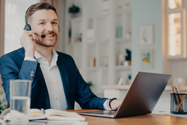 Glücklicher männlicher manager im anzug, der kopfhörer trägt und schaut, während er mit laptop arbeitet und online spricht, geschäftsmann, der online-meeting hat, während er zu hause aus der ferne arbeitet fernarbeitskonzept