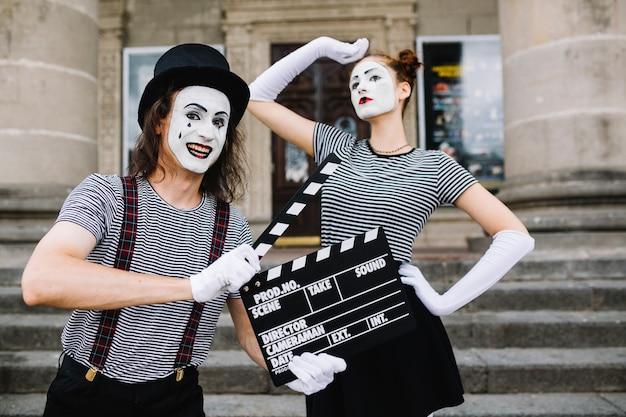 Glücklicher männlicher pantomime, der clapperboard vor der aufstellung des weiblichen pantomimen hält