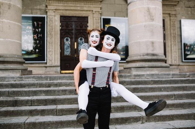 Glücklicher männlicher pantomime, der piggyback fahrt zum weiblichen pantomimen vor treppenhaus gibt