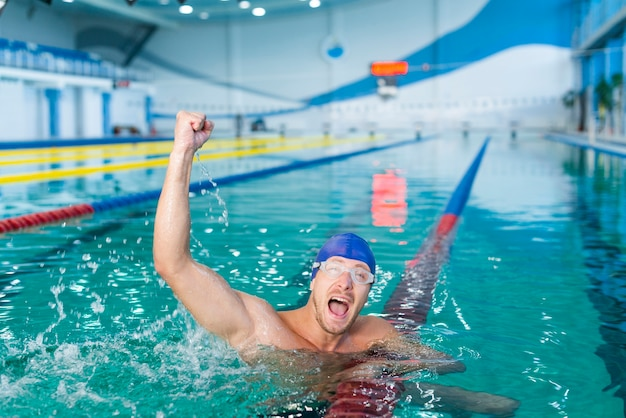 Glücklicher männlicher schwimmer, der hand im wasser anhebt