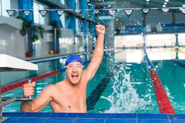 Glücklicher männlicher schwimmer, der seine hand anhebt